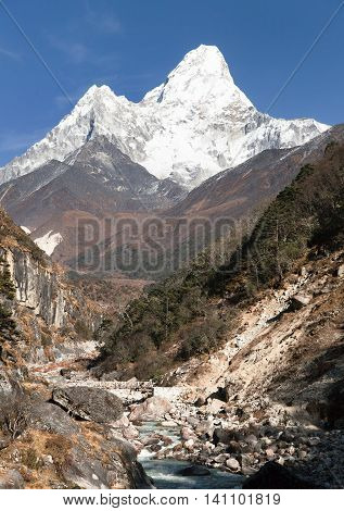 View of mount Ama Dablam with stony and wooden bridge above river - way to everest base camp - Khumbu valley - Nepal