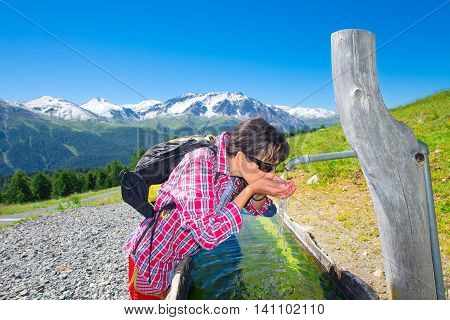Girl Hiker Quenches Thirst At The Fountain During A Mountain Trekking