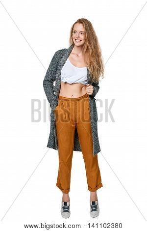 Trendy young woman in pants and long cardigan in full length smiling happy looking away, over white background