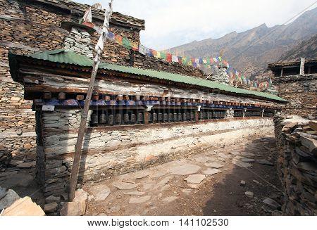 Buddhist prayer many wall with prayer wheels in nepalese village round Annapurna circuit trekking route Nepal