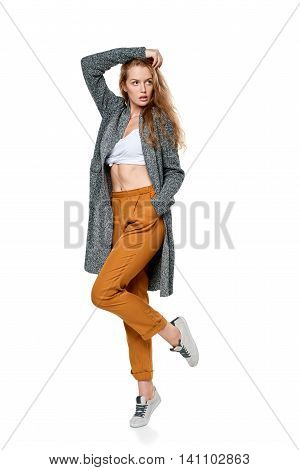 Trendy young woman in pants and long cardigan in full length posing looking away, over white background