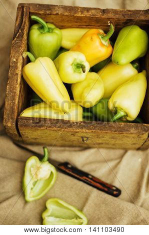 red papper on wooden table , selective focus on green part. Background with peppers