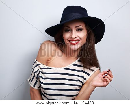 Happy Toothy Laughing Makeup Female Model In Black Elegant Hat With Red Brigh Lipstick On Blue Backg