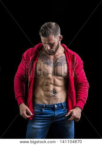 Handsome muscular man with sweater open on naked torso, standing, in studio shot