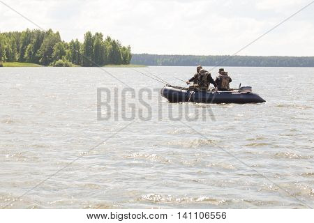 Fishermen catch fish from a boat on the lake