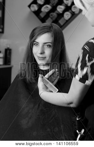 Hair cutting process. Young girl in barber shop. New hair dress