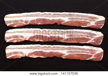 Three Strips Of Streaky Uncooked Bacon Isolated On Black  From Above.