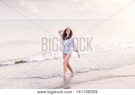 Beautiful young woman on beach at sunset wearing striped blue and white shirt and hat, smiling, holding head. Enjoying time at seaside.