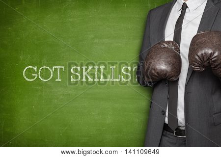 Got skills on blackboard with businessman wearing boxing gloves
