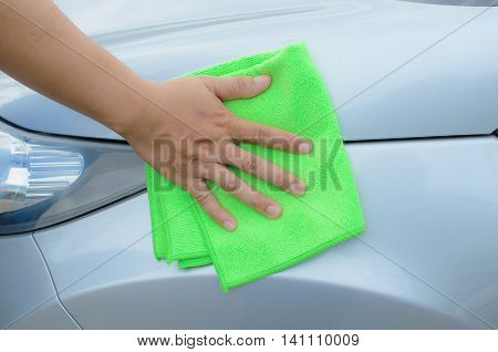 Hand with green microfiber cloth cleaning car.