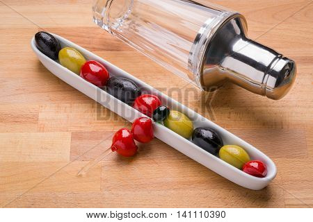Olives in dish with a martini shaker in the background