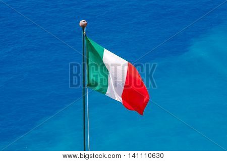The Italian national flag on a background of blue sea in the village Vernazza.