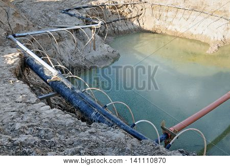The process of lowering the groundwater level. Industrial sand quarry and a metal tube around it with thin tubes directed at the ground.