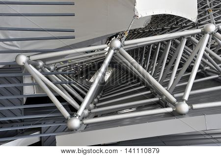 Metal spatial triangular structure close-up. The rods combined in ball nodes.