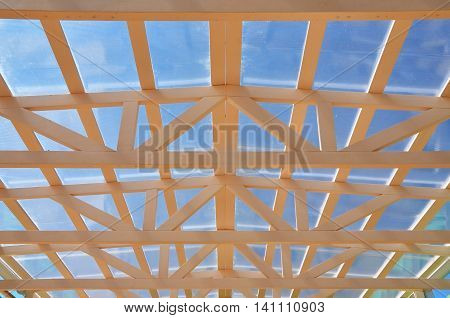 Modern roof construction. The frame of the wooden trusses and polycarbonate filling. Lookup.