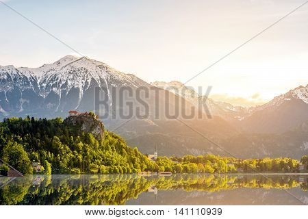 Beautiful morning landscape with castle and snowed up Alpes on the Bled lake in Slovenia.