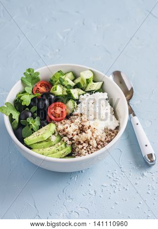 Mediterranean quinoa bowl with avocado cucumbers olives tomatoes feta cheese arugula. On a blue background. Delicious healthy vegetarian food