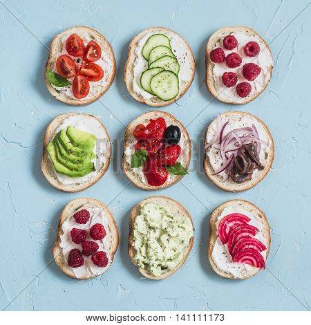 Assortment of sandwiches - sandwiches with cheese tomatoes anchovies roasted peppers raspberries avocado bean pate cucumber olives. On a blue background top view.