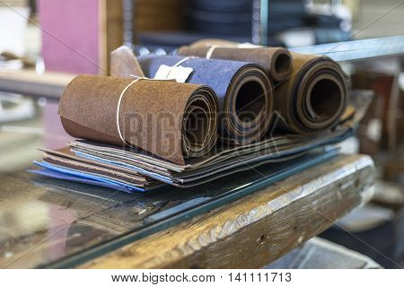 Bookbinder rolls of leather on workbench ready for use.