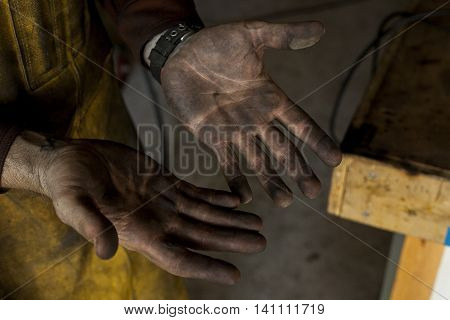 A welder's dirtied hands after a long afternoon of labor.