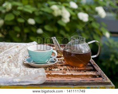 An open beehive with tea pot and tea cup with saucer on top of it flowering garden in the blurred background