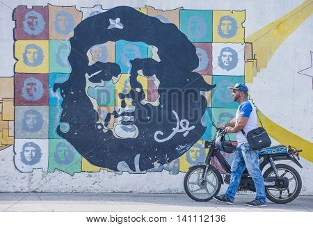 HAVANA CUBA - JULY 18 : A man with a motorcycle walking past a mural of Che Guevara in old Havana street on July 18 2016. The historic center of Havana is UNESCO World Heritage Site since 1982.