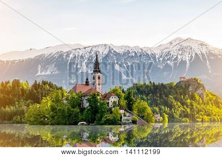 Saint Marys church on the Bled island with snowed up mountains and castle on the background in Slovenia.