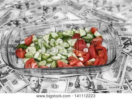 US currency spread out on a table and a bowl with fresh chopped vegetables in the center. Concept of food value selective color shot