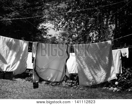 Clean clothes and laundry drying on a rope outdoors front shot in black and white