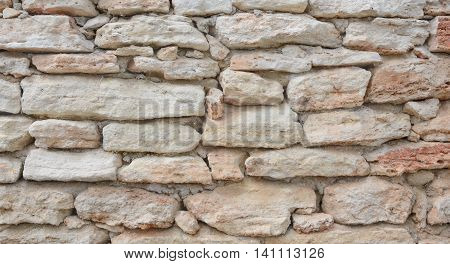 Wall from light-beige stones in a horizontal format