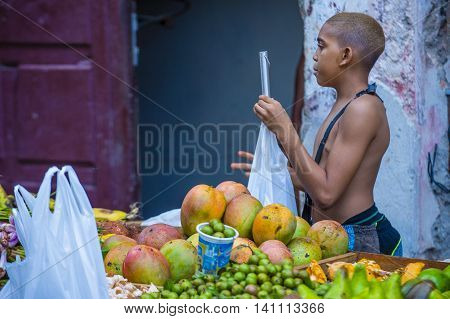 HAVANA CUBA - JULY 18 : A Cuban fruit seller in old Havana street on July 18 2016. The historic center of Havana is UNESCO World Heritage Site since 1982.