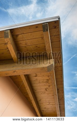 Corner of house with wooden beams against blue sky.