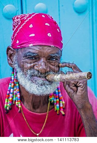 HAVANA CUBA - JULY 18 : A portrait of a Cuban man smoking cigar in old Havana street on July 18 2016. Cuba now exports more than 90 million cigars a year