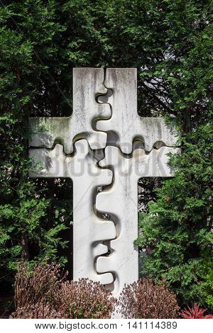 Stone cross shaped bone/puzzle surrounded by the cemetery garden.