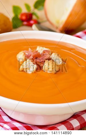 closeup of a bowl with spanish salmorejo cordobes or porra antequerana, topped with serrano ham and croutons, on a set table