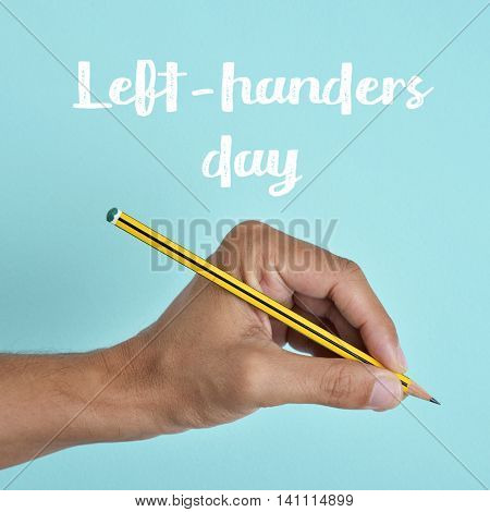 the text left-handers day and the hand of a left-handed man with a pencil, against a blue background