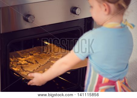 Cute Little Girl Baking Christmas Cookies In Oven