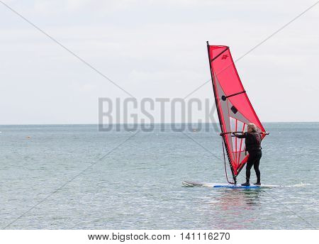 COVERACK, CORNWALL, UK - JULY 2, 2016. An elderly man keeping active by taking part in windsurfing activities on a calm ocean in Coverack, Cornwall, UK.
