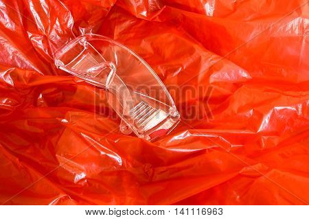 Red synthetic protective material with security glasses for safety.