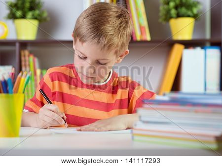 School Boy At Classroom Desk Making  Schoolwork