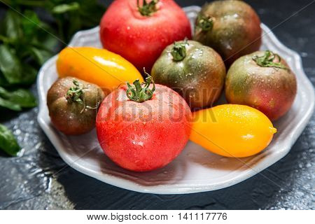Colorful tomatoes of different sizes and kinds with basil. selective focus