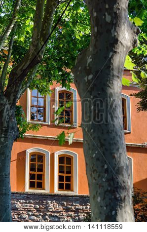 old brown house with arched windows of the trunks of plane trees, Istanbul