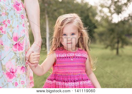 little girl standing next to her mother and holds her hand.