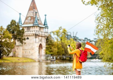 Young female traveler with austrian flag taking picture in front of Franzensburg castle in Laxenburg town. Traveling in Austria