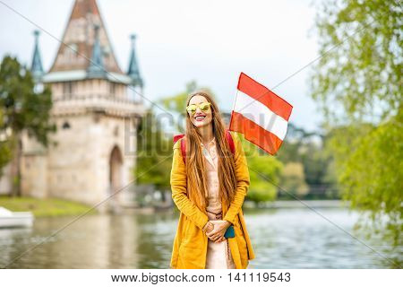 Young woman with austrian flag traveling near Franzensburg castle in Laxenburg town. Traveling in Austria