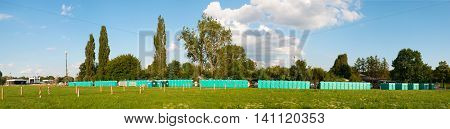 KRAKOW, POLAND - JULY 20 2016: The row of public toilets prepared for the World Youth Day 21016 on Blonia Field in Cracow and construction of the main altar far on the left
