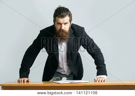 young handsome bearded man scientist or professor with long beard and teacher glasses with book or notepaper at table on grey background