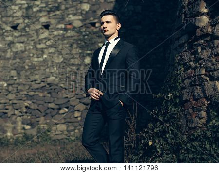 Man half face young handsome elegant model in suit with skinny necktie poses with hand in trouser pocket one leg backward outdoor on masonry background
