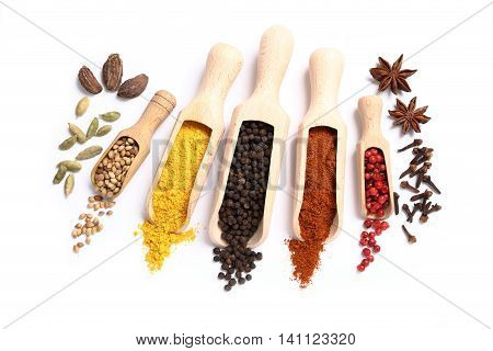 Colorful spices in wooden spoons on white background.