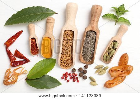 Colorful spices and herbs on white wooden background.